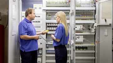 A male and a female sodexo employee standing in front of a cupboard full of switches
